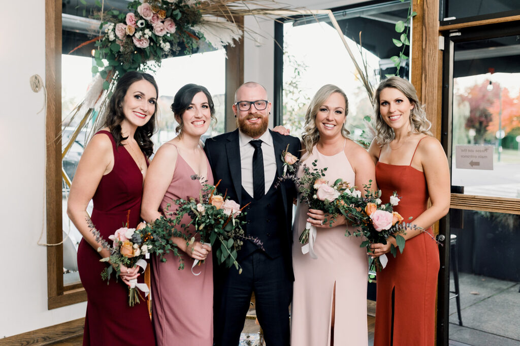 groom with bridesmaids at alter